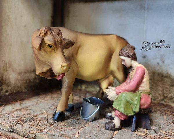 ein Bäuerin beim Melken einer Kuh als Krippenfigur aus Kunstharz