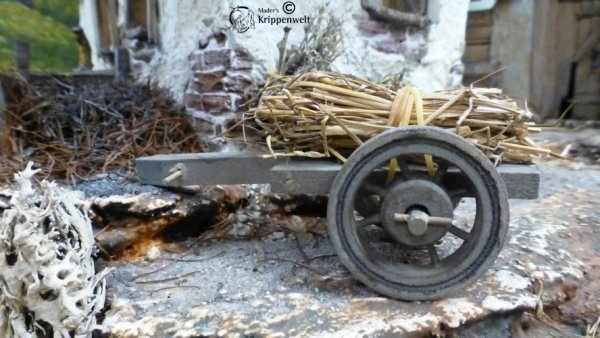 Holzkarre mit Stroh beladen als Krippenzubehör