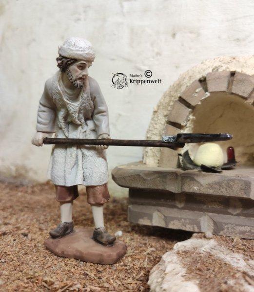 eine Bäcker mit Brotschieber beim Beladen eines Ofens